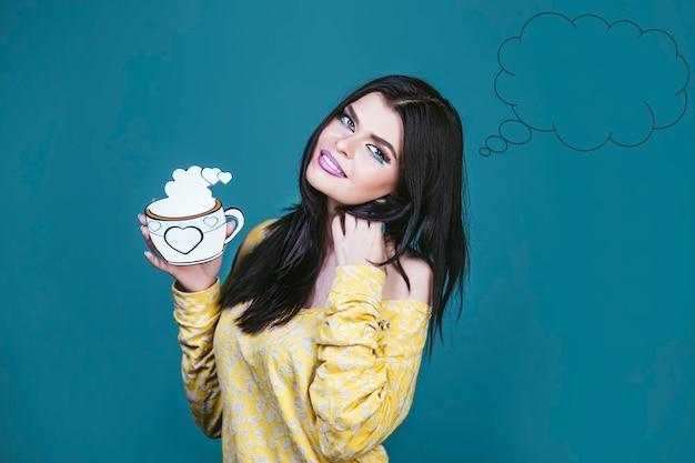 Femme modèle jeune et belle dans le style du pop art sur fond bleu avec un dessin animé tasse de thé ou de café de boisson chaude