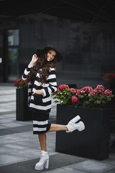 Femme modèle joyeuse avec un corps parfait et de longues jambes sexy dans une tenue moderne et un chapeau noir posant sur la rue de la ville européenne
