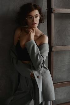 Femme modèle séduisante avec une silhouette parfaite et des lèvres charnues portant un haut cami noir et des lunettes posant près du mur gris