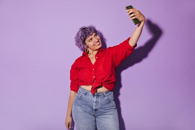 Femme moderne aux cheveux violets courts en chemise brillante prend selfie. jolie femme en tenue élégante fait de la photo.
