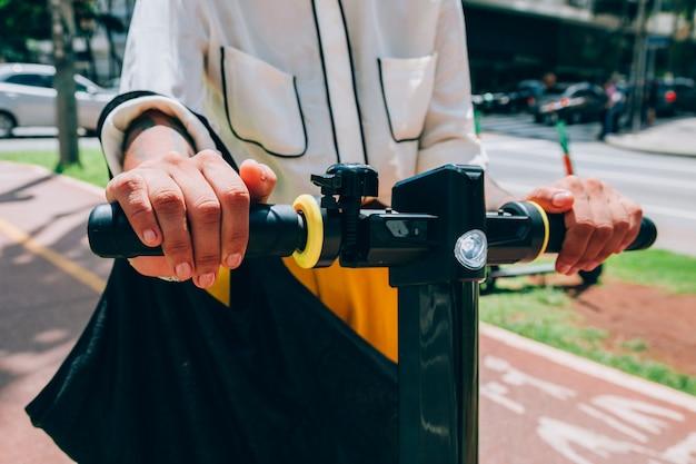 Femme moderne dans une ville avec un scooter électrique