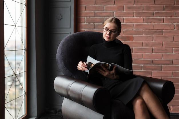 Femme moderne, délassant, sur, divan, à, magazine