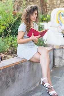 Femme moderne en lisant un livre dans le parc