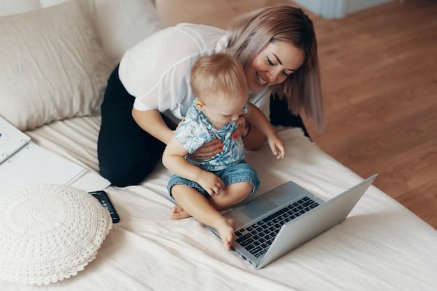 Femme moderne travaillant avec enfant. concept multitâche, indépendant et maternité