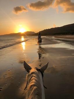 Femme montant un cheval au coucher du soleil sur la plage