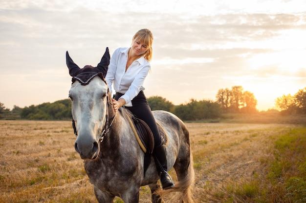 Une femme montant un cheval gris dans un champ au coucher du soleil. promenades, équitation, location. beau fond, nature en plein air. formation aux sports équestres. espace de copie. amour pour l'animal, amitié