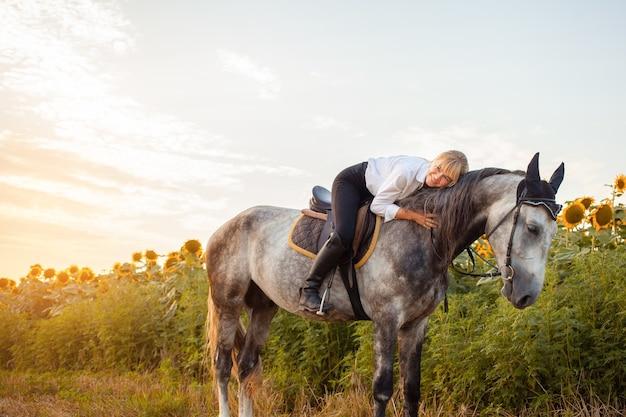 Une femme monte un cheval gris dans un champ au coucher du soleil. liberté, beau fond, amitié et amour pour l'animal. entraînement sportif équestre, location et vente de chevaux, randonnées, équitation, promenades. câlins