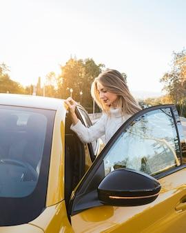 Femme, monter, dans, a, voiture, à, porte ouverte