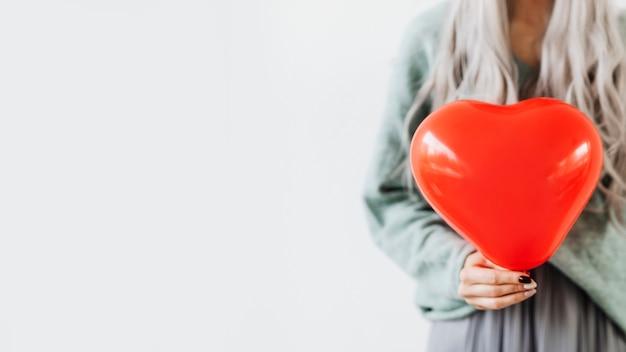 Femme montrant un ballon rouge coeur