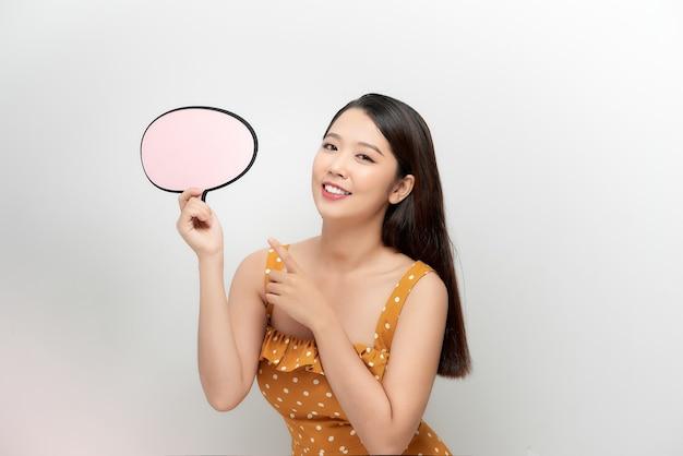 Femme montrant une bannière de bulle de dialogue à l'air heureux et pointant son doigt dessus