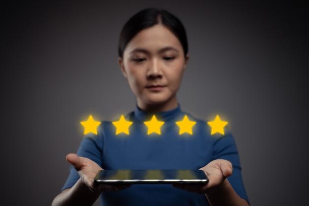 Femme montrant des commentaires sur la tablette, des critiques avec effet d'hologramme icône cinq étoiles