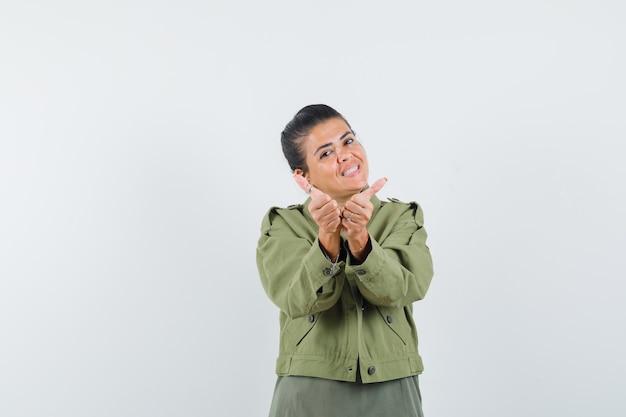 Femme montrant deux pouces vers le haut en veste, t-shirt et à la joyeuse