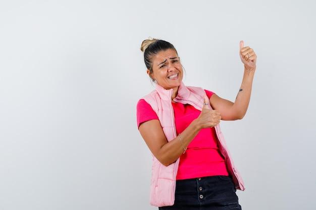 Femme montrant double pouce levé en t-shirt, gilet et à la joyeuse