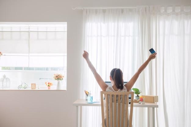 Femme montrant du bonheur après avoir fait des achats en ligne avec le style de vie new normal pour l'auto-quarantaine pendant l'épidémie de maladie à virus corona (covid-19).