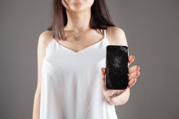 Femme montrant l'écran du téléphone cassé sur gris