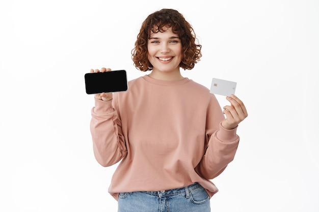 Femme montrant un écran de smartphone horizontal avec carte de crédit bancaire, recommandant une application mobile, debout sur blanc