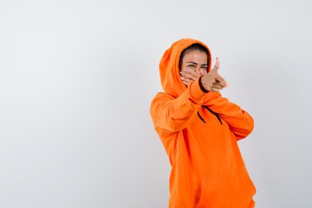 Femme montrant un geste d'arme à feu dans un sweat à capuche orange et à l'heure
