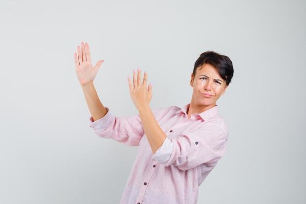 Femme montrant le geste de côtelette de karaté en vue de face de chemise rose.