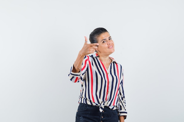 Femme montrant le geste du pistolet en chemise, jupe et à la joyeuse