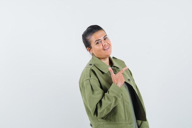 Femme montrant le geste du pistolet en veste, t-shirt et à la confiance.