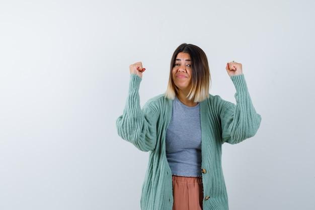 Femme montrant le geste gagnant dans des vêtements décontractés et à la chance, vue de face.