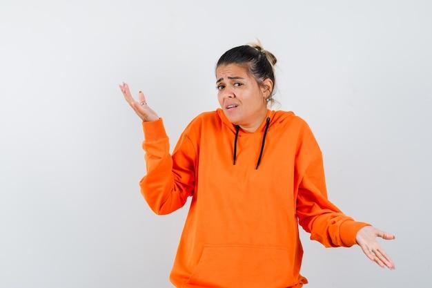 Femme montrant un geste impuissant en sweat à capuche orange et à la confusion