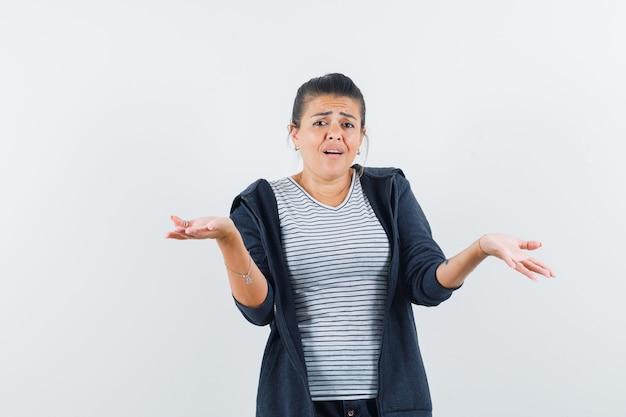 Femme montrant un geste impuissant en t-shirt