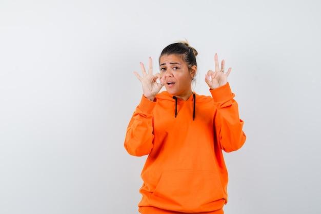 Femme montrant un geste ok en sweat à capuche orange et ayant l'air confiant