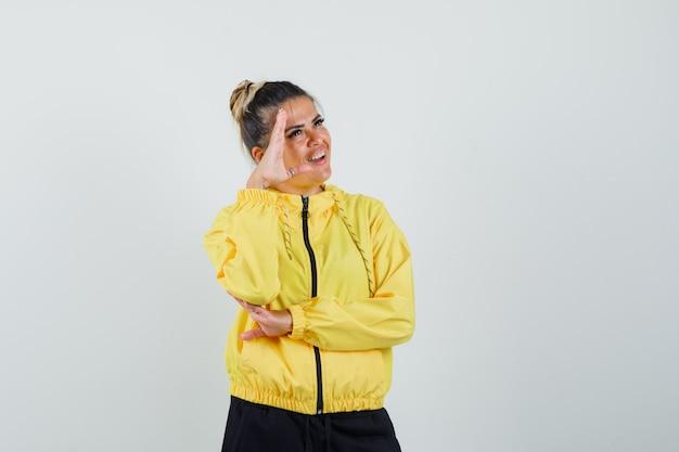 Femme montrant le geste de salut en costume de sport et à la joyeuse. vue de face.