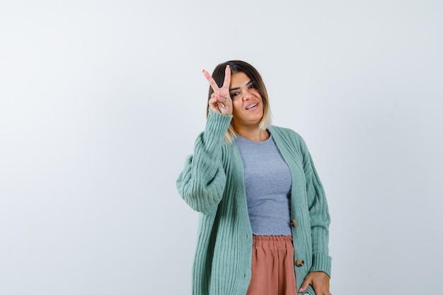 Femme montrant le geste de la victoire dans des vêtements décontractés et à la vue de face, confiant.