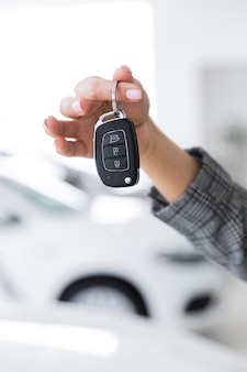 Femme montrant des gros plan de clés de voiture