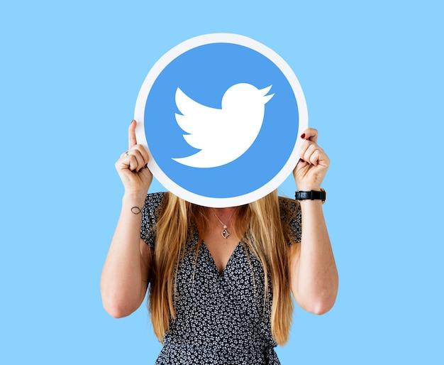Femme montrant une icône twitter