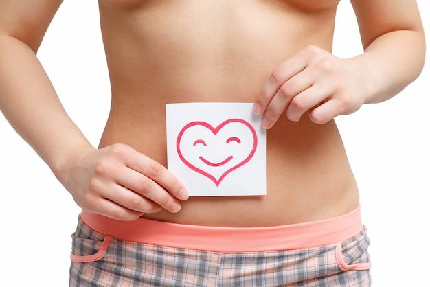 Femme montrant un joli signe en forme de coeur devant son ventre