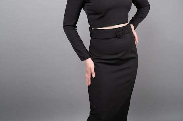Femme montrant une longue jupe noire.