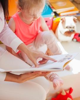 Femme montrant des photos de filles dans un livre
