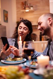 Femme montrant des photos de mari sur smartphone pendant l'anniversaire de la relation festive. adultes assis à table dans la cuisine naviguant, cherchant, utilisant des smartphones, internet, célébrant