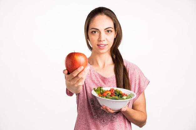 Femme montrant une pomme et regardant la caméra