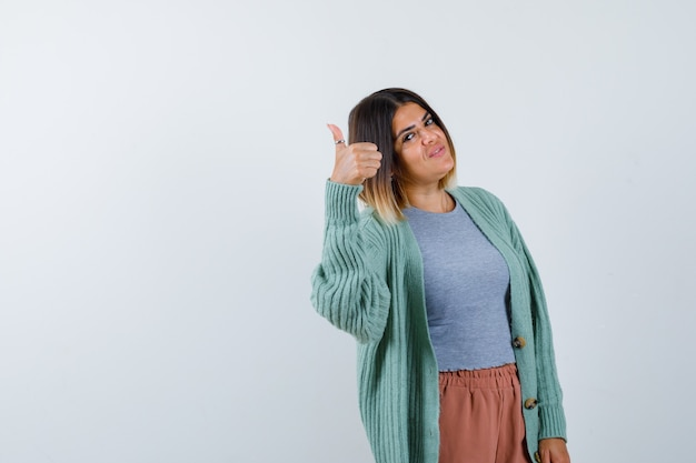 Femme montrant le pouce vers le haut dans des vêtements décontractés et regardant confiant, vue de face.