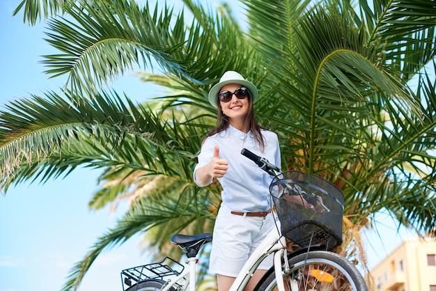 Femme montrant les pouces vers le haut avec vélo