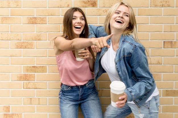 Femme montrant quelque chose à son amie
