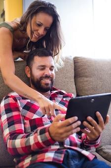 Femme montrant quelque chose à son mari sur l'écran d'une tablette numérique