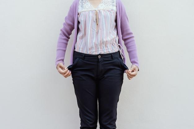 Femme montrant sa poche vide sur fond de mur.