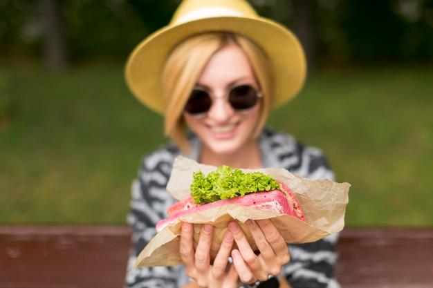 Femme montrant un sandwich et souriant
