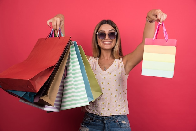 Femme montrant ses sacs à provisions sur le mur rouge.