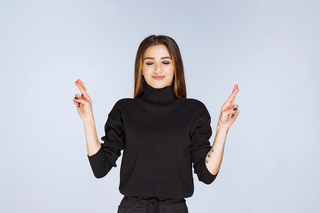 Femme montrant un signe de croix à la main.
