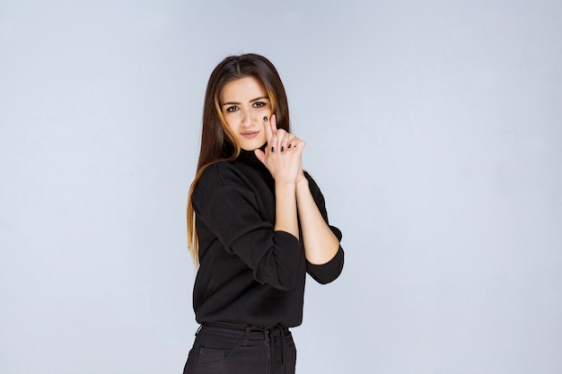 Femme montrant le signe du pistolet dans la main.