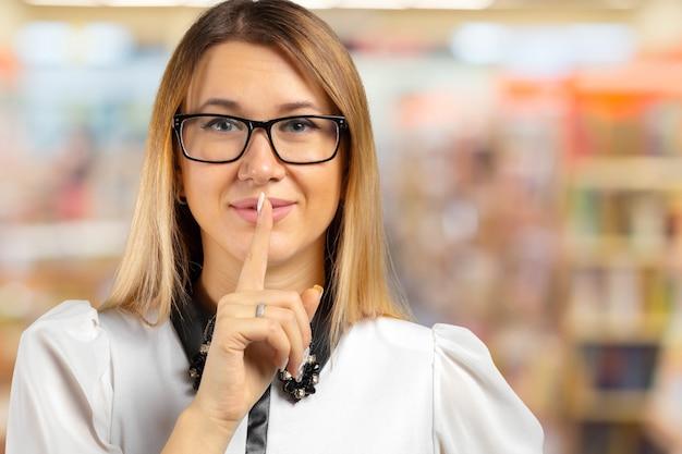 Femme montrant le signe de silence avec son index.