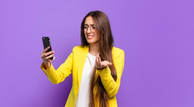 Femme montrant son écran cellulaire.