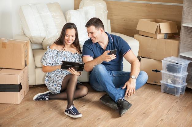 Femme montrant à son mari les nouveaux rideaux sur sa tablette. couple créant des souvenirs