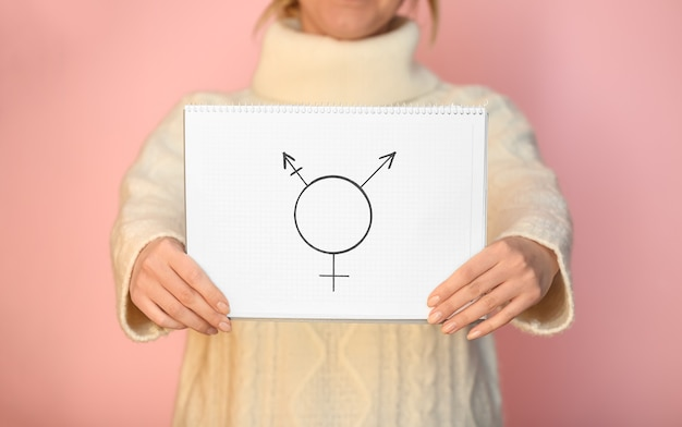 Femme montrant le symbole des transgenres sur la surface de couleur, gros plan
